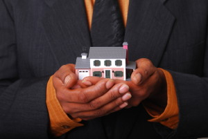 African-American male hands holding a miniature house.